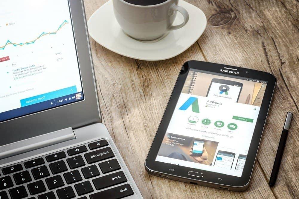 laptop, tablet, kávé íróasztalon, grafikonokkal