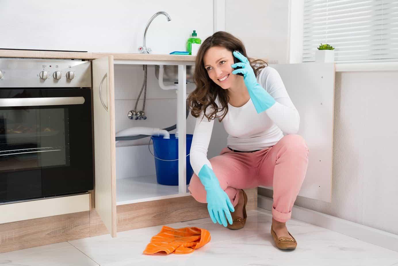 nő telefonál a mosogató előtt
